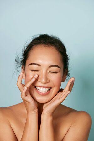 Schönheitsgesicht. Lächelnde asiatische Frau, die gesundes Hautporträt berührt