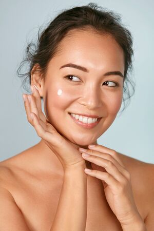 Face skin care. Woman applying cosmetic cream on skin portrait