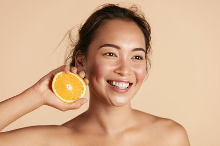 Beauty. Smiling woman with radiant face skin and orange portrait Фото со стока