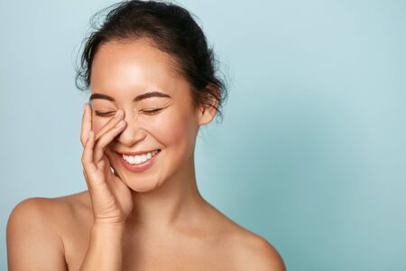 Schönheitsgesicht. Lächelnde asiatische Frau, die gesundes Hautporträt berührt. Schönes glückliches Mädchenmodell mit frischer leuchtender hydratisierter Gesichtshaut und natürlichem Make-up auf blauem Hintergrund im Studio. Hautpflegekonzept Standard-Bild