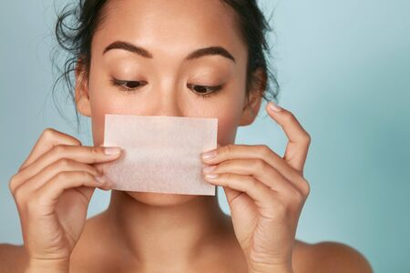 Skin care. Woman holding facial oil blotting paper portrait