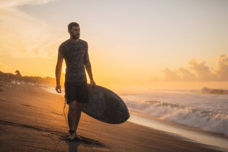 Surfing. Surfer Carrying Surfboard On Ocean Beach. Man Silhouette At Beautiful Sunrise In Bali. Stock fotó