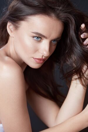 Beautiful Woman. Girl Touching Hair Close Up Portrait. Blue-Eyed Brunette With Smooth Perfect Skin And Natural Makeup. Young Model Looking Away. Banque d'images