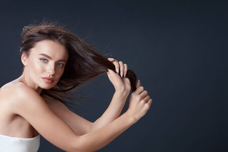 Beautiful Girl. Woman Holding Hair Portrait. Blue-Eyed Brunette With Smooth Perfect Skin And Natural Makeup. Young Model Looking At Camera. Banque d'images - 147977478
