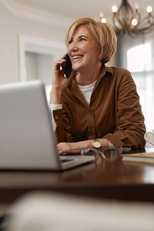 Businesswoman Homework. Female With Laptop. Mature Woman In Brown Jacket And Eyeglasses Talks On Phone.