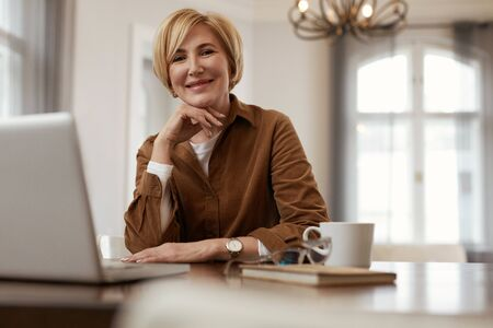 Female With Laptop. Senior Blonde Woman In Brown Jacket Sits At The Desk With Laptop And Cup. Businesswoman Homework Concept. Stock fotó