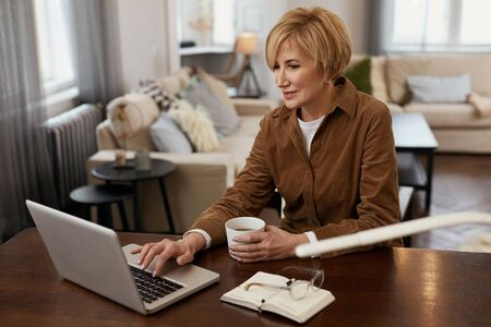 Female With Laptop. Remote Homework Concept. Mature Woman In Brown Jacket Reads From Computer And Drinks From Cup. Stock fotó