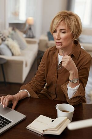 Businesswoman. Female With Laptop. Mature Woman Remote Homework Concept. Model in Brown Jacket And Eyeglasses Uses Notebook.