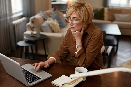 Businesswoman Remote Homework Concept. Female With Laptop. Mature Woman In Brown Jacket Drinks From Cup In Front Of Notebook. Stock fotó