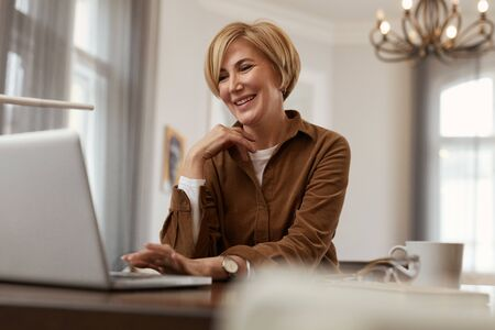 Businesswoman. Female With Laptop. Mature Blonde Woman In Brown Jacket Sits At The Desk With Computer And Cup. Remote Homework.
