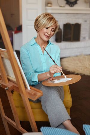 Female Painter. Mature Woman Draws A Painting Using Colour Palette. Indoors Creative Hobby.