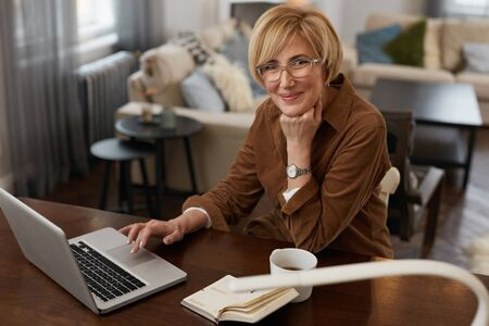 Businesswoman. Female Uses Laptop. Mature Woman Remote Homework Concept. Older Model in Brown Jacket And Eyeglasses Uses Notebook. Stockfoto