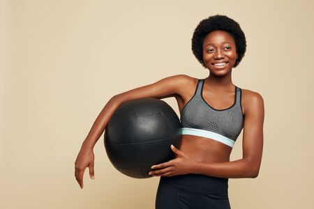 Fitness. Sporty African Woman Portrait. Smiling Female In Sportswear Holding Black Fitness Ball And Looking Away. Sport For Natural Beauty. Фото со стока