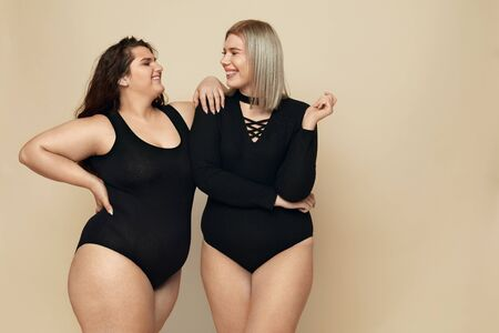 Plus Size Models. Full-figured Women Portrait. Smiling Brunette And Blonde In Black Bodysuits Posing On Beige Background. Body Positive As Lifestyle.