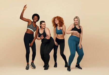 Different Race. Diversity Figure And Size Women Full-Length Portrait. Group Of Multicultural Friends In Sportswear Posing On Beige Background. Body Positive As Lifestyle.