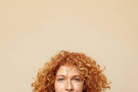 Redhead Woman. Ginger Hair Girl Cropped Close Up Portrait. Beautiful Blue-Eyed Female With Curly Hairdo Looking At Camera.