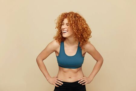 Redhead Woman. Fit Girl Portrait. Smiling Beautiful Female In Sportswear Keeping Hands On Hips. Fitness For Active Lifestyle.