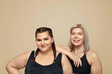 Body Positive. Plus Size Models Portrait. Full-Figured Women In Sportswear On Beige Background. Fitness For Active Lifestyle.