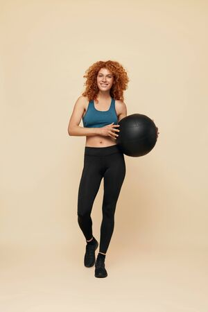 Fitness Woman. Smiling Redhead Girl Full-Length Portrait. Female In Sportswear And Sneakers Holding Fitness Ball.