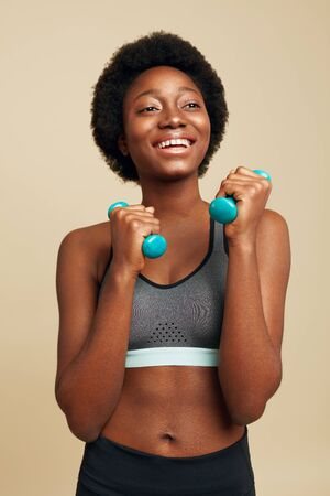 Fitness. Sporty African Woman Portrait. Smiling Female Exercising With Dumbbells And Looking Away. Sport For Natural Beauty.
