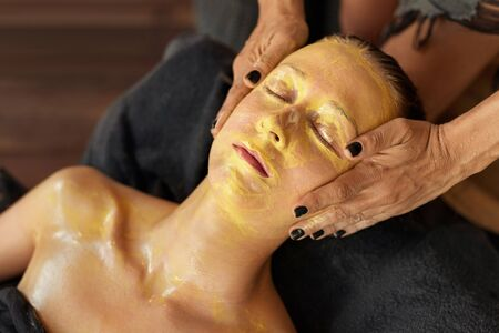Facial Treatment. Resting Woman On Skin Care Procedure. Beautician Applying Yellow Face Mask During Spa Relaxation.