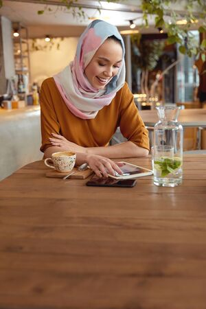 Muslim Woman. Young Girl In Hijab Portrait. Beautiful Female Sitting In Cafe And Working On Tablet. Smiling Model Looking At Screen And Reading.