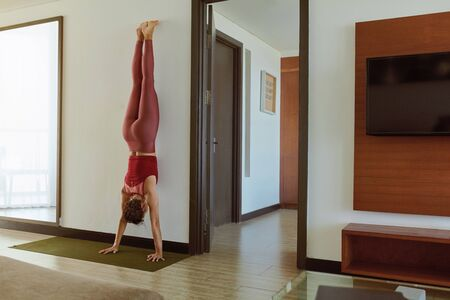 Yoga At Home. Woman Doing Handstand In Living Room During Social Isolation. Brunette In Fashion Sportswear Practicing Adho Mukha Vrksasana Near Wall. Sport Routine For Active Lifestyle.