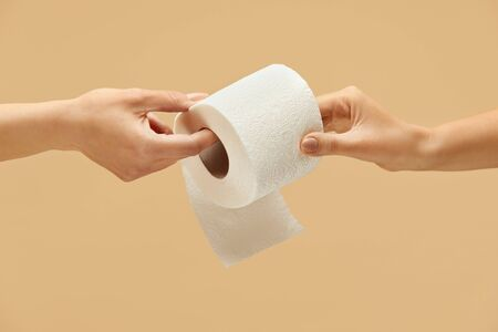 Toilet Paper. Roll In Female Hand On Beige Background. One Woman Gives Tissue Paper To Another. Stop Panic Of COVID Spreading And Using High-Quality Personal Hygiene Product For Staying Healthy.