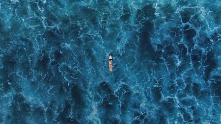 Top View. Surfer On White Surfboard Swimming On Beautiful Ocean Background. Blue Water With Waves.