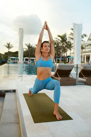 Yoga. Woman In Warrior Pose Asana. Brunette In Blue Sportswear Practicing Virabhadrasana Near Pool. Yoga Exercising As Lifestyle.