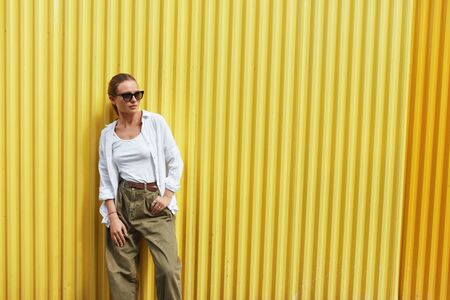 Stylish Girl. Portrait Of Sexy Woman. Fashion Model In Casual Clothes And Sunglasses Standing Against Yellow Metal Fence. Female In White Shirt And Top Tank. Urban Lifestyle.