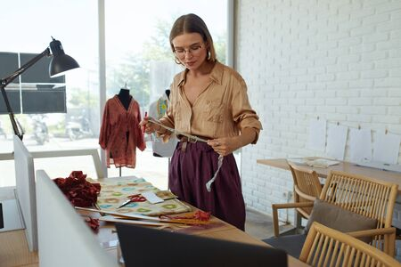 Job. Fashion Designer At Workshop. Beautiful Tailor Measuring Fabric For New Dress. Success Self Employed Woman In Stylish Clothes Working At Atelier. Professional Dressmaker At Own Studio.