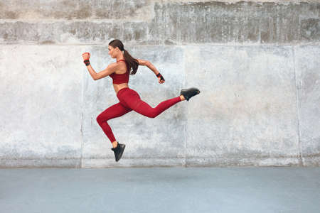 Fitness Girl Jumping. Outdoor Workout Against Concrete Wall At Stadium. Fashion Sporty Female With Strong Sexy Body In Dynamic Action Pose. Sport For Active Urban People.