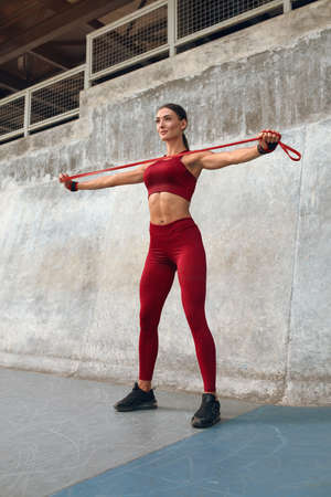 Woman. Workout With Resistance Band For Strong Muscular Body. Fitness Girl In Fashion Sporty Outfit Doing Stretching Exercise On Stadium. Sport As Lifestyle For Active Urban People. Archivio Fotografico