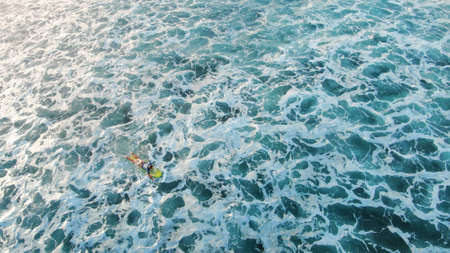 Aerial View. Surfer On Surfboard Against Blue Ocean Background. Surfing Man Floating On Board In Foam Sea. Water Sport For Active Lifestyle At Tropical Vacation.