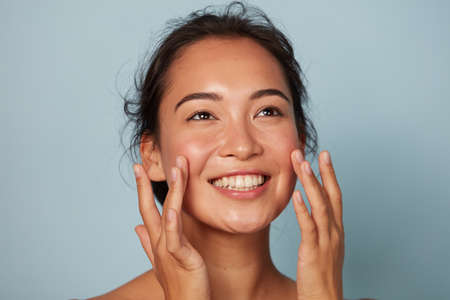 Beauty face. Smiling asian woman touching healthy skin portrait Stock fotó