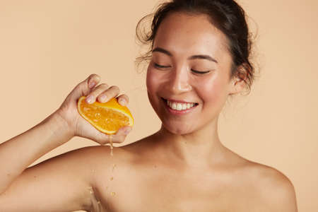 Beauty. Woman with radiant face skin squeezing orange portrait