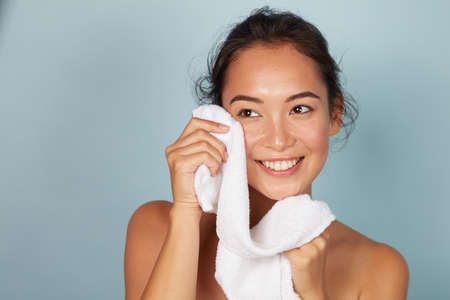 Washing face. Closeup of woman cleaning skin with towel portrait