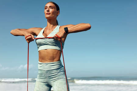 Fitness Girl On Beach Portrait. Stretching Workout With Resistance Loop On Tropical Ocean Background. Sporty Woman With Strong Muscular Body In Fashion Sportswear Training On Summer Vacation.
