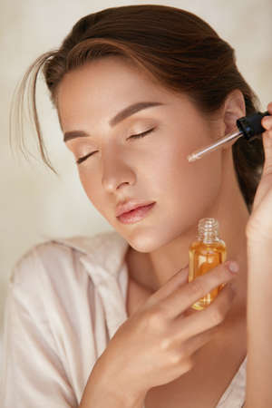 Skin Care. Woman Applying Essential Oil With Dropper On Face. Natural Cosmetic Product For Hydrated, Glowing And Healthy Facial Derma. Portrait Of Beauty Model With Perfect Skin.