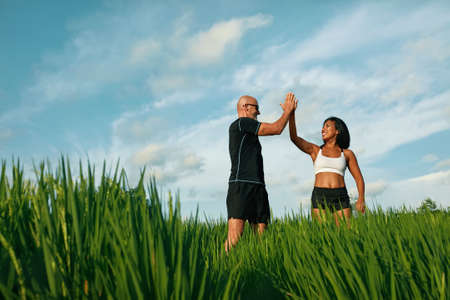 Sportive Peoples Giving High Five Among Green Grass Portrait. Caucasian Man And Asian Woman Standing On Paddy Field After Running Workout.