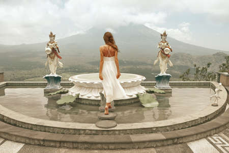 Beautiful Girl Posing On Fountain Against Agung Volcano In Bali, Indonesia.