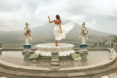 Beautiful Girl In White Dress Fluttering In Wind Looking At Agung Volcano In Bali, Indonesia. 版權商用圖片