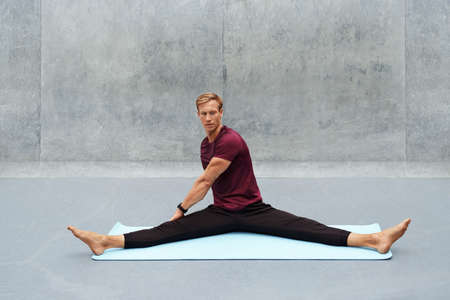 Young Man Stretching On Yoga Mat Against Concrete Wall Outdoors. Handsome Caucasian Sportsman With Strong Muscular Body In Fashion Sportswear Warming Up Before Intense Workout.