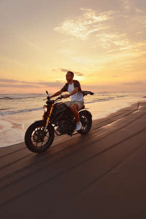 Man And Motorcycle On Ocean Beach At Beautiful Tropical Sunset. Handsome Biker On Motorbike On Sandy Coast In Bali, Indonesia. Stock Photo