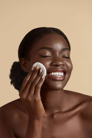 Portrait close up of beautiful black girl touch her clean face with cotton pad. Smiling young woman with closed eyes. Concept of face skin care. Isolated on beige background. Studio shoot Stock Photo