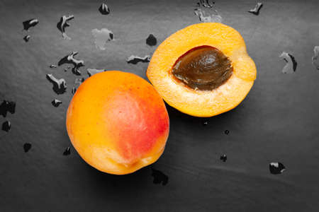 Top view wet apricots on a wet dark background. Fresh juicy ruddy apricots on a dark clay plate with drops splashed with water. Close-up healthy organic food. Stock fotó