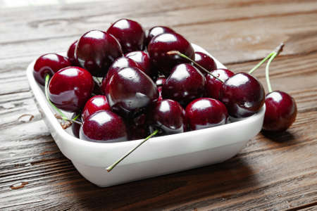 Fresh ripe juicy sweet cherries in a white plate on a wooden background. Wet sweet cherries with water drops. Foto de archivo