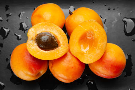 Wet apricots on a wet dark background. Fresh juicy ruddy apricots on a dark clay plate with drops splashed with water. Close-up healthy organic food.