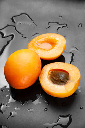 One whole and two half wet apricots on a wet dark background. Fresh juicy ruddy apricots on a dark clay plate splashed with water drops. Close-up healthy organic food.